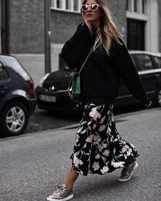 На девушке черный свитер с капюшоном, черное платье с цветочным принтом и воланами длины миди, кеды, поясная зеленая сумка и очки.