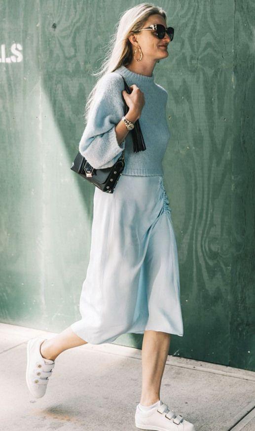 Бирюзовый короткий свитер, надетый поверх такого же цвета атласного прямого платья ниже колена, в сочетании с белыми кедами, черной сумкой и очками.