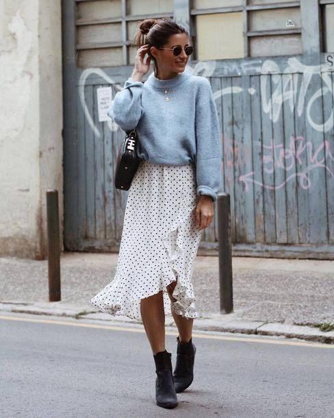 На девушке голубой короткий свитер, надетый поверх белого платья в черный мелкий горошек с воланами и разрезом ниже колена, в сочетании с черными ботинками, черной сумкой и очками.