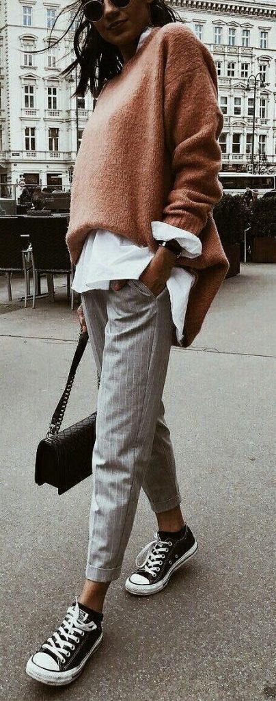 На девушке белая длинная рубашка, персиковый объемный свитер, серые прямые брюки в полоску, черные кеды, маленькая черная сумочка и очки.