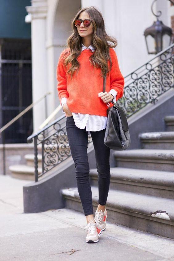 На девушке белая рубашка в синюю полоску, оранжевый свитер, черные скинни, кроссовки, большая поясная сумка и очки.