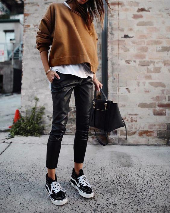 На девушке белая рубашка, коричневый свитер с круглым вырезом, кожаные брюки, высокие черные кроссовки на белой подошве, черная сумка.