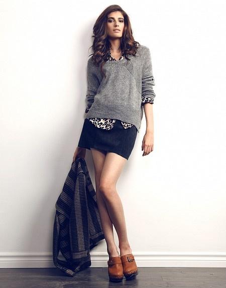 На девушке рубашка с леопардовым принтом, серый свитер с круглым вырезом, прямая черная юбка-мини, коричневые кожаные ботинки с ремешком.