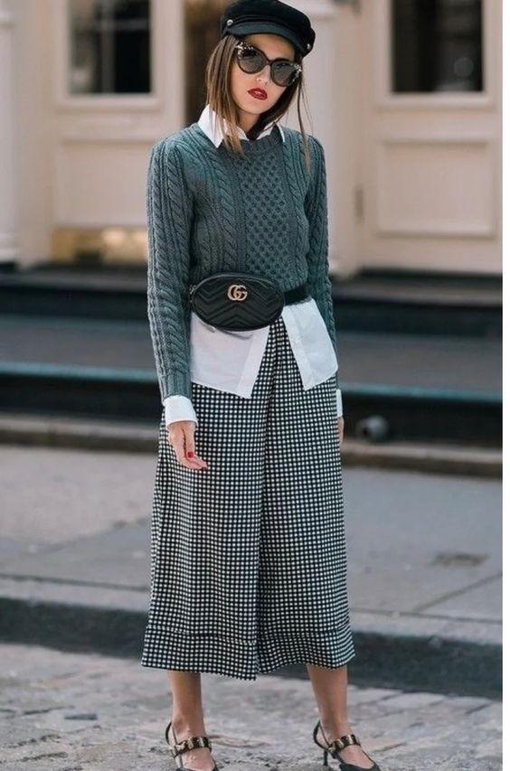 На девушке длинная белая рубашка, темно-зеленый укороченный свитер с ажурным узором, черно-белые кюлоты с принтом виши, черные туфли на маленьком тонком каблуке. Образ дополнен кепи, черной круглой поясной сумкой и очками.