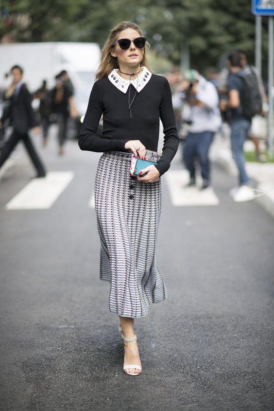 На девушке черный тонкий свитер, белая рубашка с украшенным воротником, прямая юбка-миди, белые босоножки на каблуке, очки и клатч.