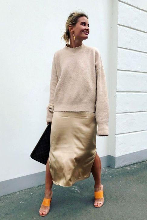 На девушке бежевый свитер оверсайз, атласная золотая юбка миди с разрезами по бокам, оранжевые босоножки с открытой пяткой и прозрачными вставками, черный большой клатч.