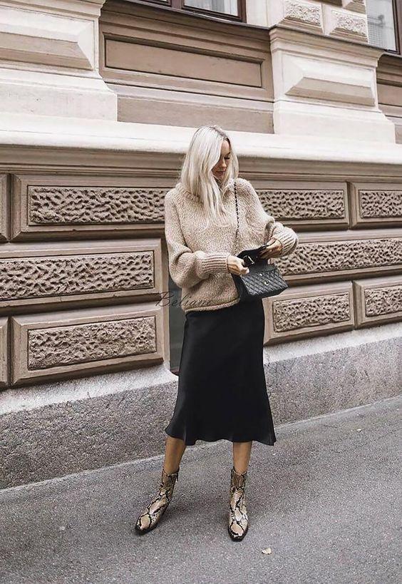 Бежевый свободный вязаный свитер в сочетании с черной свободной атласной юбкой ниже колена, высокими ботинками с анималистическим принтом, черной поясной сумкой.
