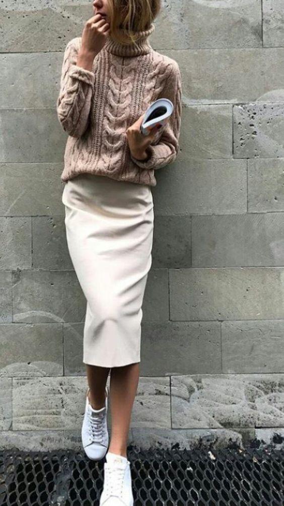 На девушке нежно-розовый свитер крупной вязки с объемный горлом, белая юбка-карандаш длины миди и белые кеды.