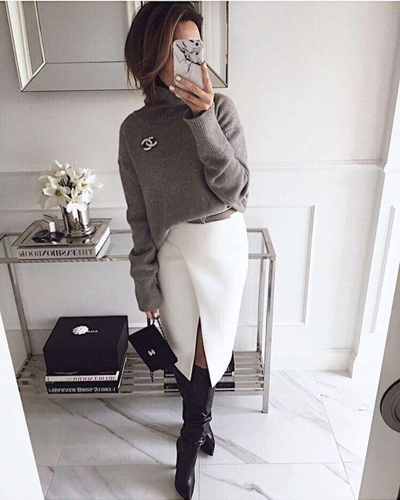 """На девушке серый свитер, украшенный брошью, белая юбка-карандаш ниже колена с разрезом, черные кожаные сапоги """"гармошкой"""", маленькая черная сумочка."""