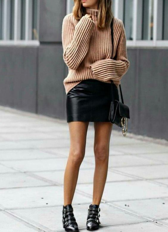 Бежевый свитер оверсайз в сочетании с кожаной прямой юбкой-мини, черными ботинками с ремешками, кожаной сумкой.