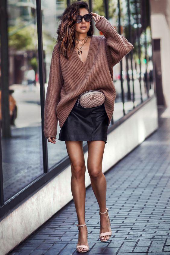 На девушке коричневый свитер оверсайз с глубоким V-образный вырезом, заправленный в кожаную прямую юбку-мини, в сочетании с бежевыми босоножками на каблуке, поясной круглой сумкой и аксессуарами.