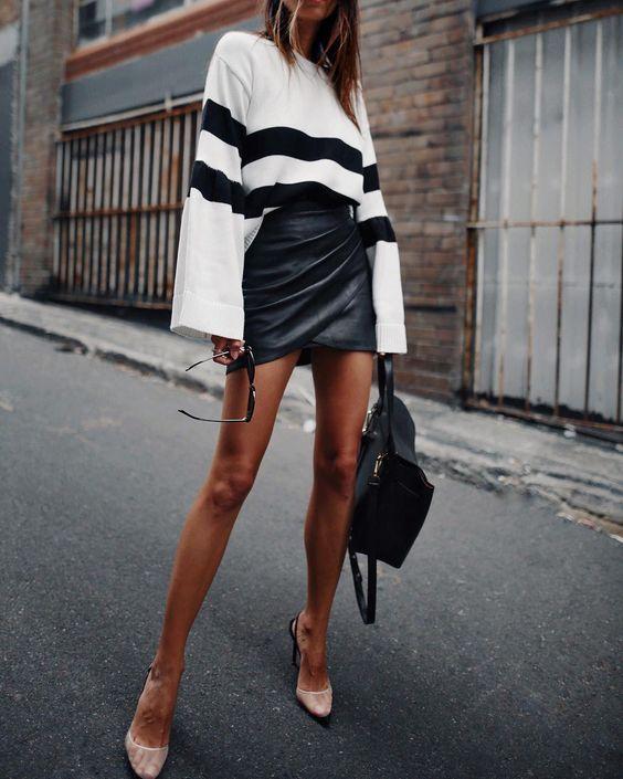 На девушке белый свитер с черными полосками и широкими рукавами, черная облегающая кожаная юбка-мини на запах, туфли с полупрозрачной сеткой и открытой пяткой на высоком тонком каблуке и черная сумка.