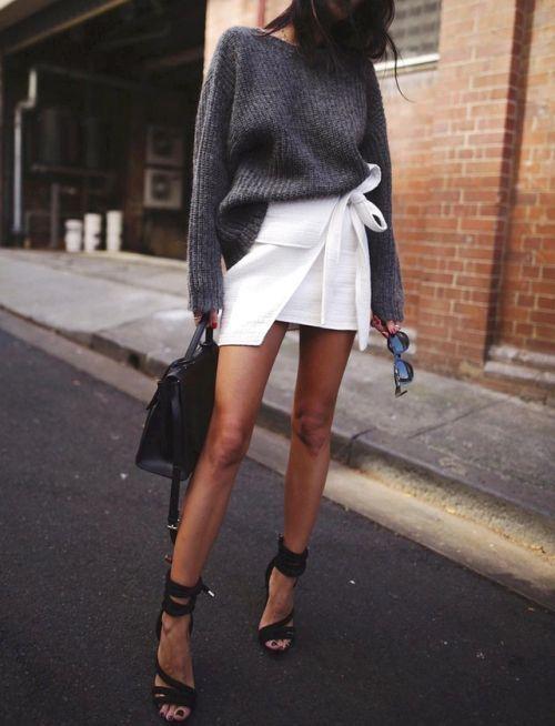 На девушке серый вязаный свитер, частично заправленный в короткую белую юбку с поясом и асимметричной формой, черные босоножки, сумка и очки.