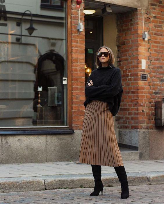 Черный свитер оверсайз в сочетании с коричневой юбкой-плиссе длины миди и замшевыми ботфортами на каблуке. Образ дополнен очками.