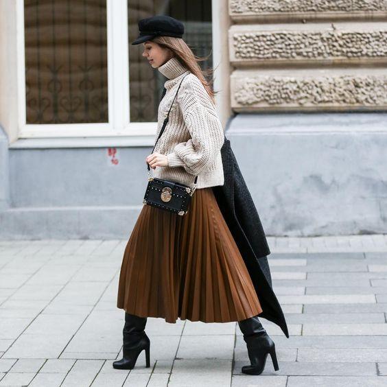 """На девушке бежевый свитер крупной вязки с ажурным узором и объемным горлом, кожаная коричневая юбка-плиссе длины миди, черные кожаные сапоги """"гармошкой"""" на высоком каблуке, черный кепи, поясная сумка и серое пальто."""