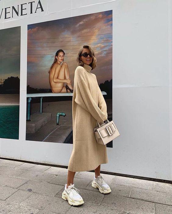 На девушке бежевое платье-свитер оверсайз длины миди, белые объемные кроссовки, сумка квадратной формы и очки.