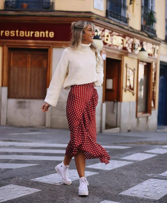 На девушке белый свитер с объемным горлом, красная юбка-миди в белый горошек и с рюшами, белые кеды.