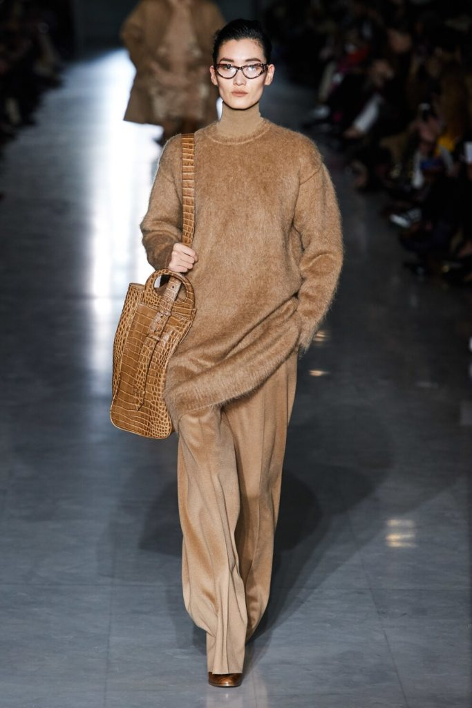 На девушке бежевый свитер оверсайз, надетый поверх такого же цвета гольфа, свободны бежевые брюки-палаццо из бархата, большая поясная сумка и очки.