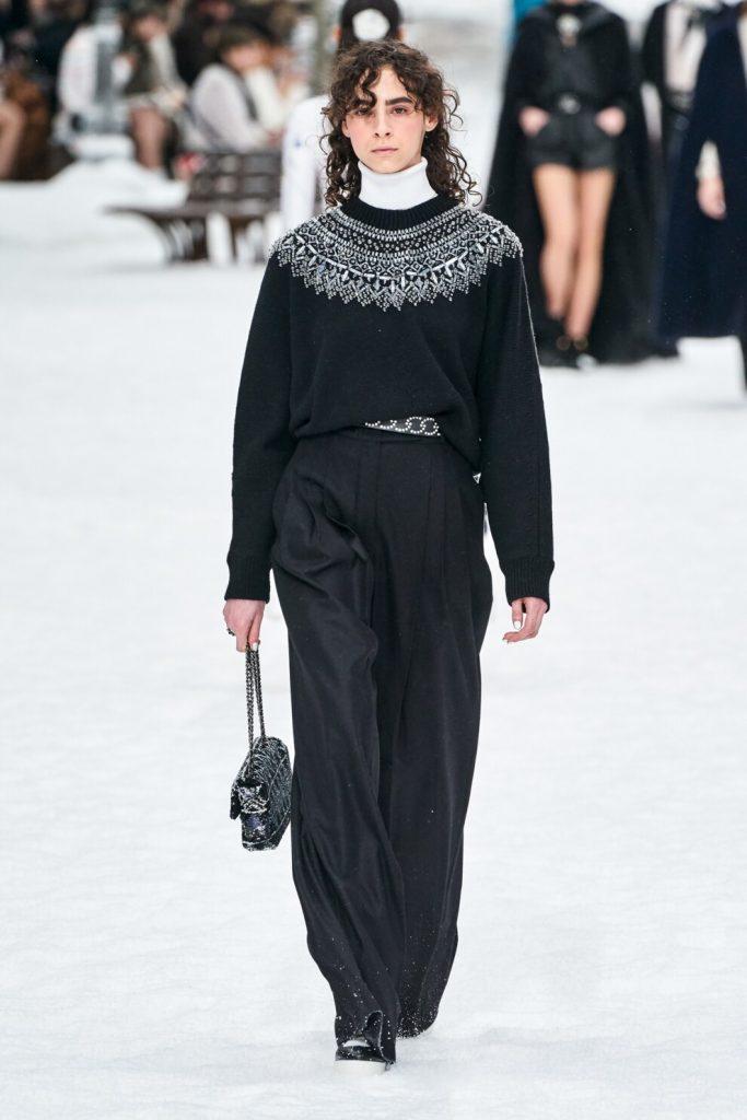 На девушке белый гольф, черный свитер с узором, заправленный в широкие черные брюки-палаццо.