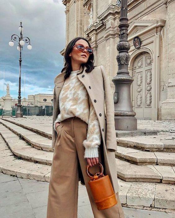 Белый свитер с бежевым узором в сочетании с светло-коричневыми кюлотами, пальто, очками и коричневой сумкой необычной формы.