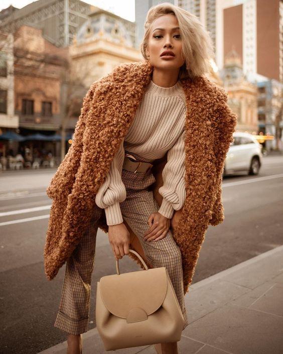 На девушке белый свитер, бежевые прямые укороченные брюки в клетку, коричневая шуба из искусственного меха и бежевая сумка.