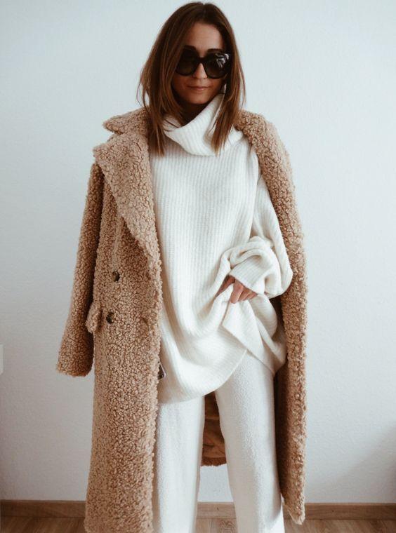 Белый свитер оверсайз с объемным горлом в сочетании с белыми трикотажными брюками прямого кроя, бежевой длинной шубой из искусственного меха и черными очками.