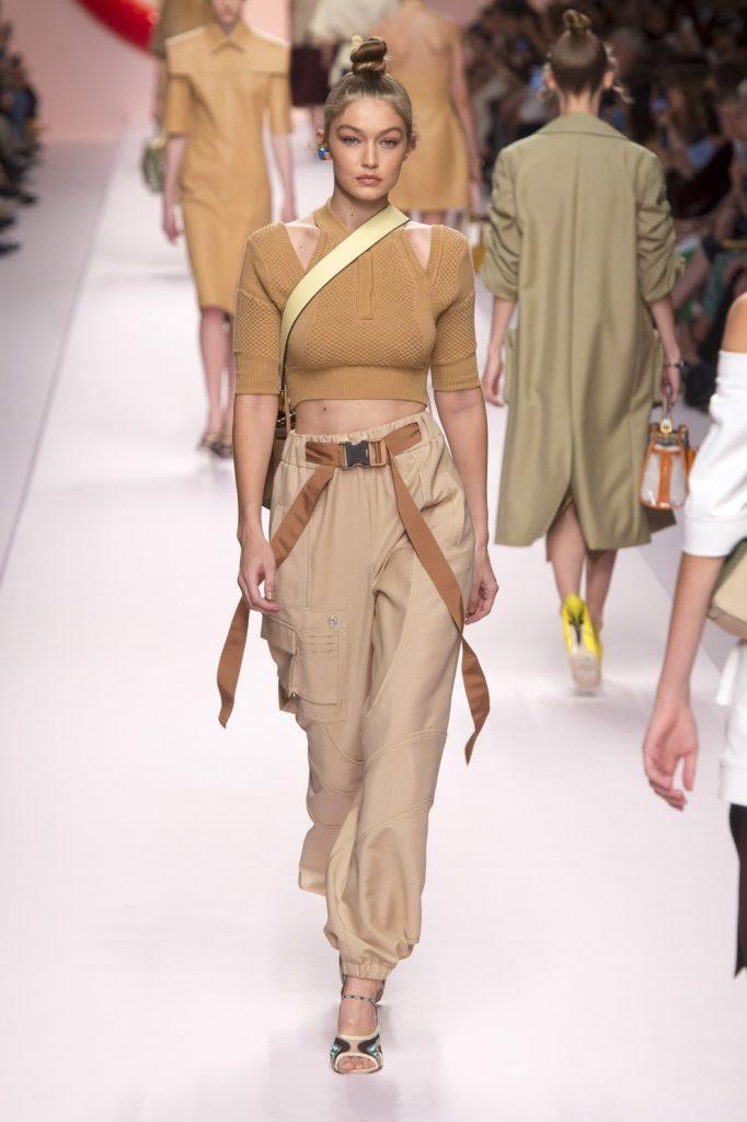 На девушке бежевый укороченный облегающий свитер с вырезами на плечах, светло-коричневые брюки-карго на манжетах, босоножки с открытым носом.