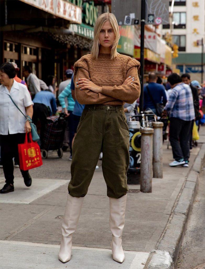 Бежевый свитер крупной вязки и объемными плечами в сочетании с объемными зелеными брюками и высокими белыми сапогами.