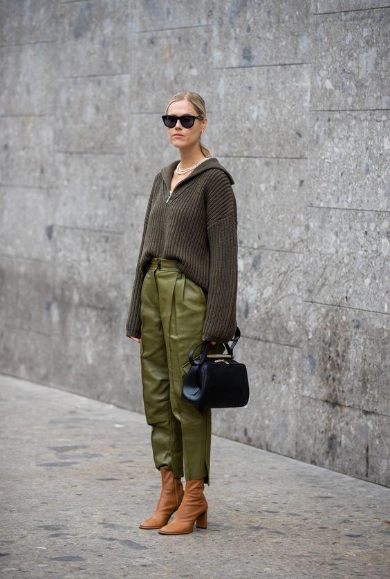 На девушке свитер оверсайз с глубоким V-образным вырезом, кожаные зеленые брюки прямого кроя, коричневые ботинки с заостренным носом на каблуке, черные очки и кожаная сумка.