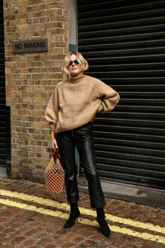 Бежевый свитер оверсайз в сочетании с черными кожаными брюками и ботинками-носками на каблуке.