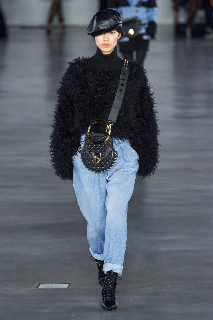 На девушке черный свитер оверсайз, голубые бананы, черные ботинки на шнуровке с заостренным носом, черная поясная сумка.