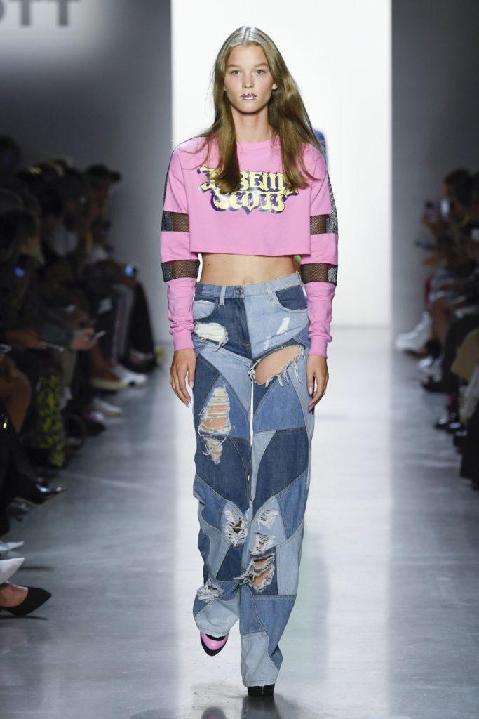 Розовый укороченный свитер с надписью и вставками в виде сетки в сочетании с прямыми длинными джинсами в стиле пэчворк.