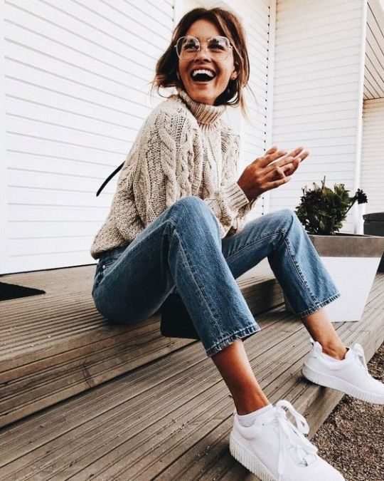 На девушке бежевый свитер крупной вязки с ажурным узором, прямые голубые джинсы и аккуратные белые кроссовки.
