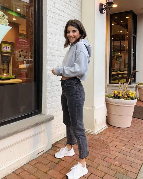 Серый укороченный свитер с капюшоном в сочетании с черными прямыми джинсами с средней посадкой, белыми кроссовками.
