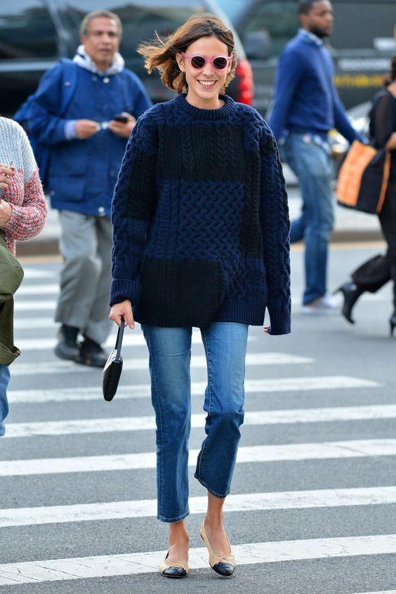 На девушке черно-синий свитер оверсайз, синие прямые джинсы, бежевые балетки, маленькая черная сумка и очки с розовой оправой.