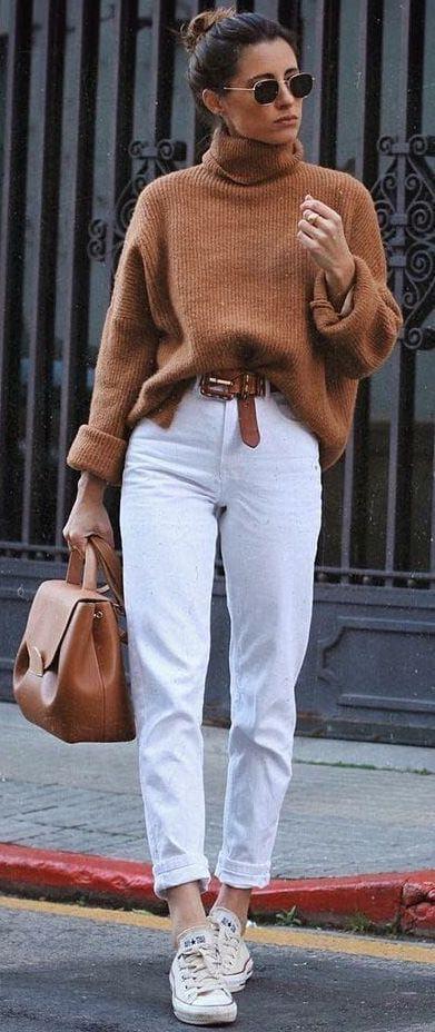 Коричневый свитер с объемным горлом, белые прямые джинсы с коричневым поясом, в сочетании с белыми кедами, коричневой сумкой и черными очками.