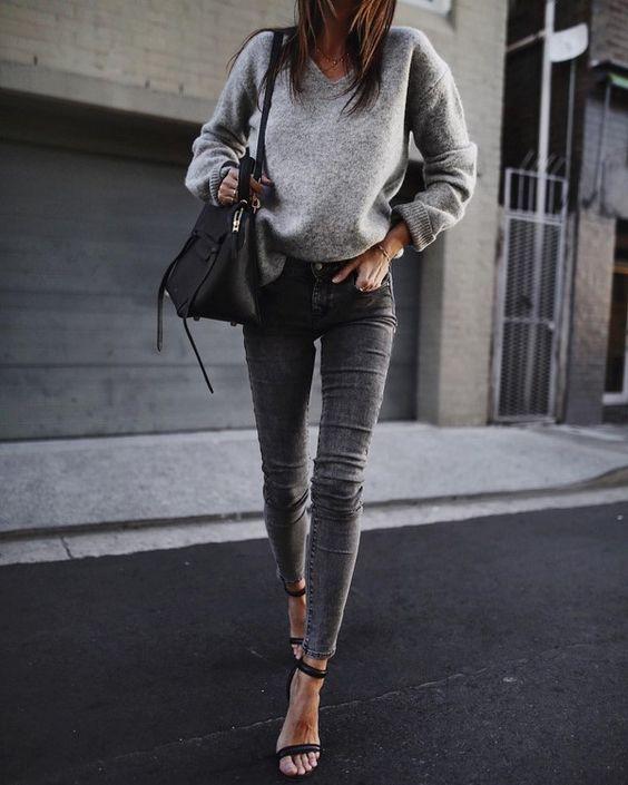 На девушке серый свитер с объемными рукавами, серые джинсы-скинни, черная кожаная сумка и босоножки на каблуке.
