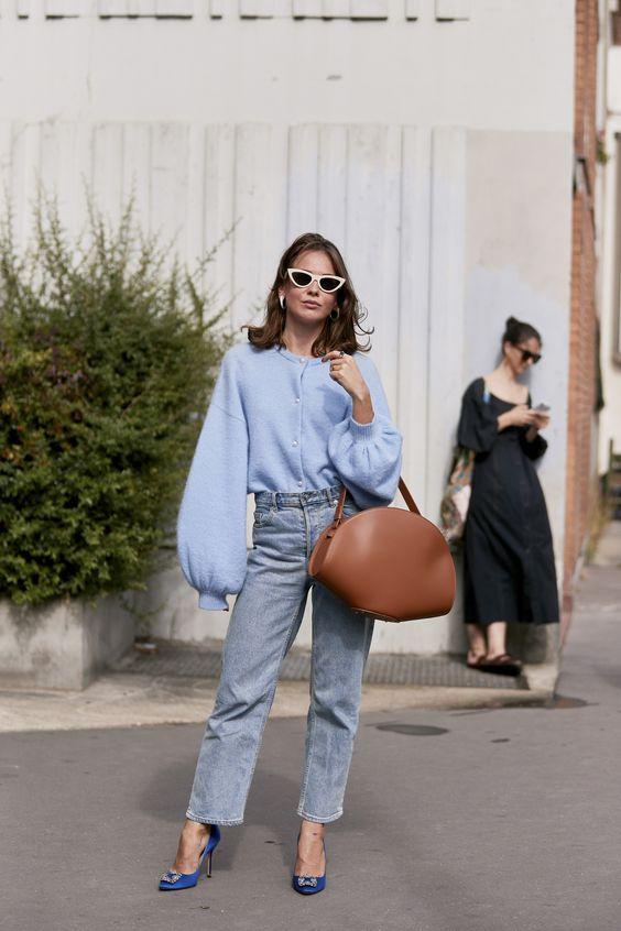 На девушке небесно-голубой свитер оверсайз на пуговицах, с объемными рукавами, прямые голубые джинсы, синие туфли на высоком каблуке, коричневая кожаная сумка и черные очки с белой оправой.