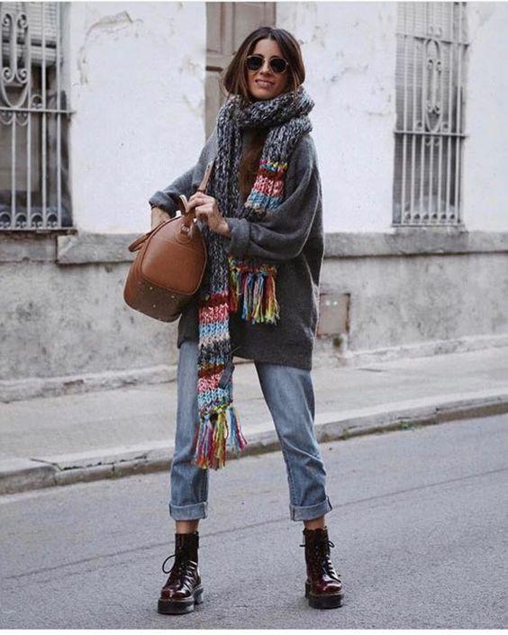 Девушка надела серый свитер оверсайз, прямые синие джинсы с подворотами, коричневые мартинсы на шнуровке, яркий длинный шарф. Образ дополнила коричневой сумкой и очками.
