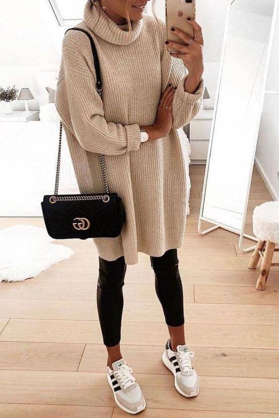 На девушке бежевый свитер оверсайз, кожаные леггинсы, светло-серые кроссовки и поясная черная сумка-клатч.