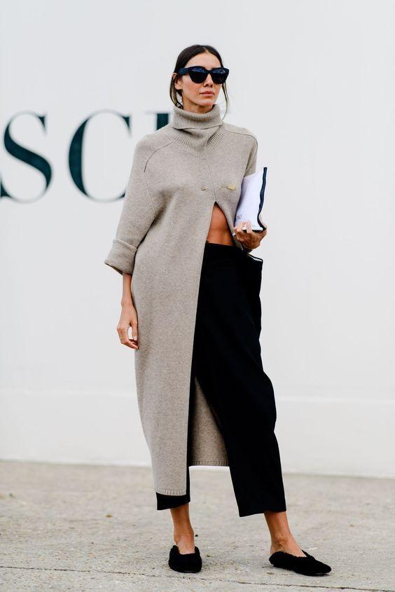 Серый свитер оверсайз длины миди с разрезом и горлом в сочетании с черными свободными брюками, туфлями на плоской подошве с заостренным носом и открытой пяткой, очками.