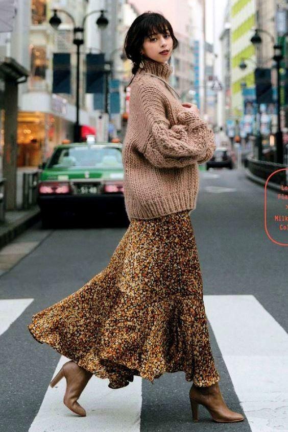 На девушке объемный бежевый свитер крупной вязки, надетый поверх пестрого платья-миди с цветочным принтом и воланами, в сочетании с бежевыми сапоги с заостренным носом и на высоком толстом каблуке.