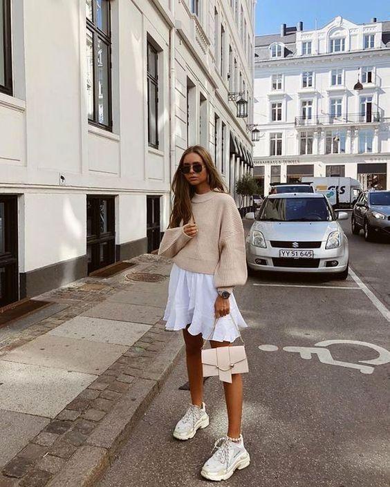 На девушке бежевый свитер с объемными рукавами, белая пышная юбка-мини, массивные белые кроссовки, нежно-розовая сумка и черные очки.