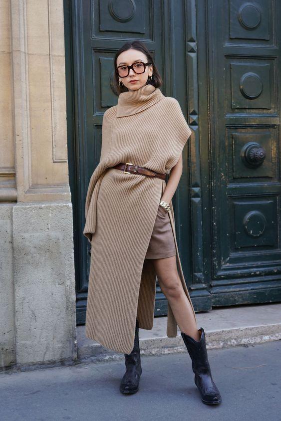 На девушке бежевый длинный свитер асимметричной формы с разрезами по бокам, подчеркнутый коричневым поясом, светло-коричневая мини-юбка, черные ковбойские сапоги, очки.