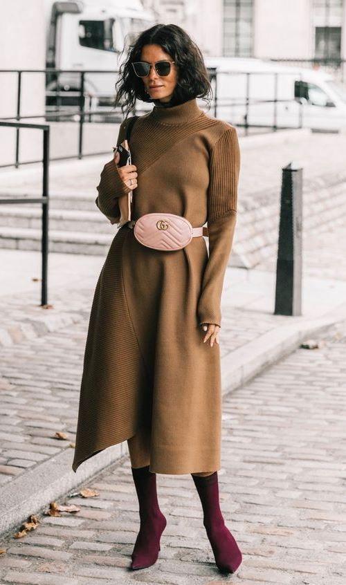 Коричневое длинное платье-свитер, нежно-розовая поясная круглая сумка, длинные бордовые ботильоны-носки с заостренным носом, черные очки.