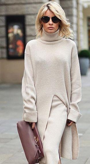 На девушке белый длинный свитер с разрезом и объемным горлом, трикотажная юбка-карандаш белого цвета, сумка-клатч и очки.