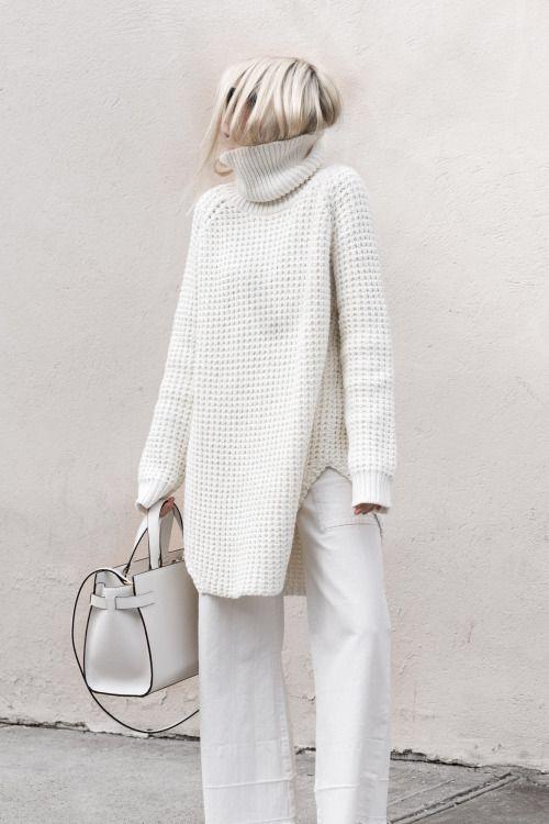 На девушке белый объемный длинный свитер крупной вязки, белые брюки прямого кроя, сумка белого цвета.