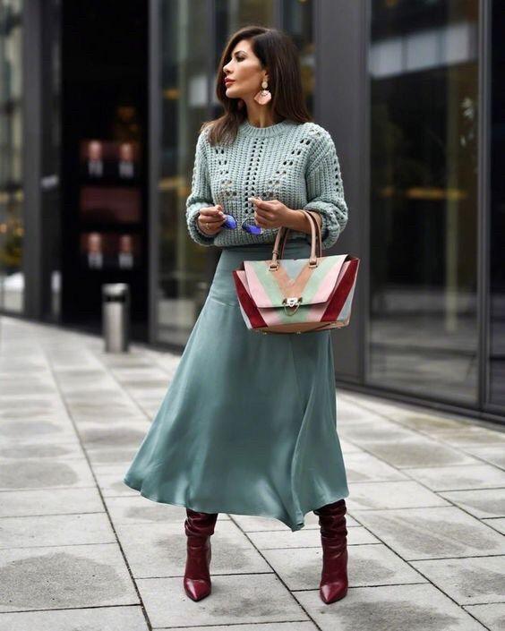 """На девушке голубой укороченный свитер крупной вязки, небесно-голубая атласная свободная юбка-миди, бордовые сапоги """"гармошка"""", цветная сумка и очки."""