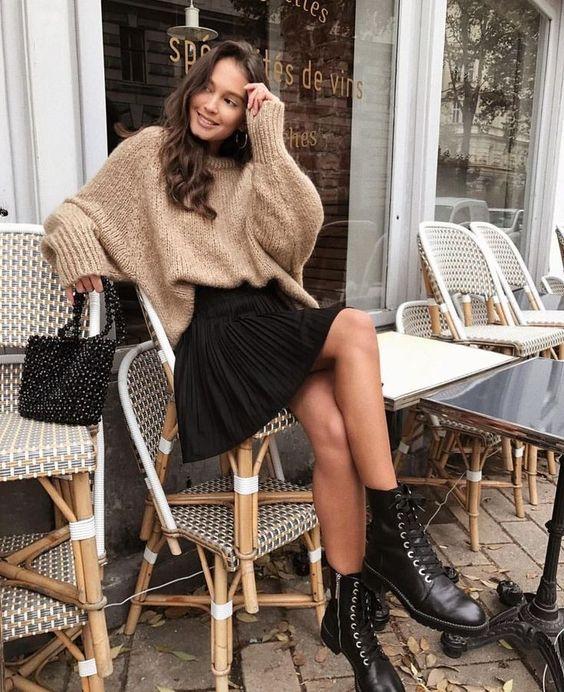 Девушка надела бежевый свитер оверсайз из плотной нити, черную расклешенную юбку-мини, грубые кожаные ботинки на шнуровке и черную маленькую сумочку.