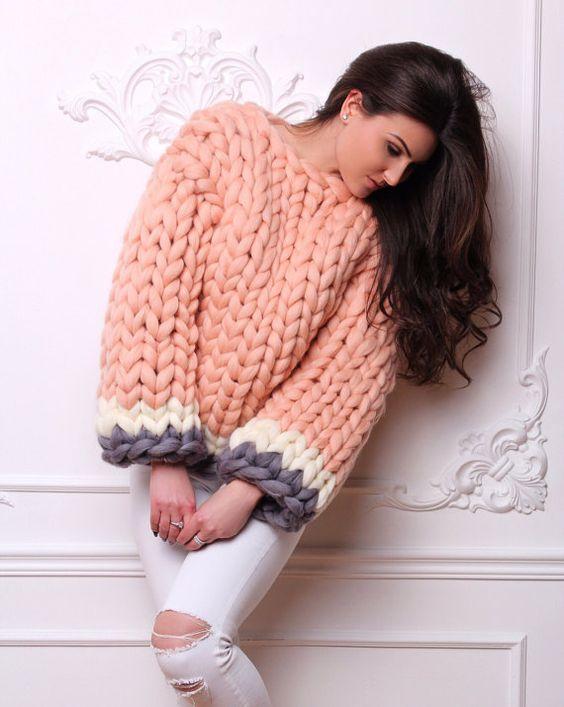 На девушке нежно-розовый свитер крупной вязки и белые джинсы-скинни.